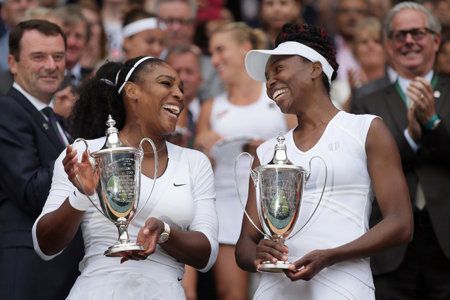 Serena Williams, left, and Venus Williams of the U.S hold their trophies after winning the women's doubles final during the Wimbledon Tennis Championships in London, Saturday, July 9, 2016. (Tim I ...