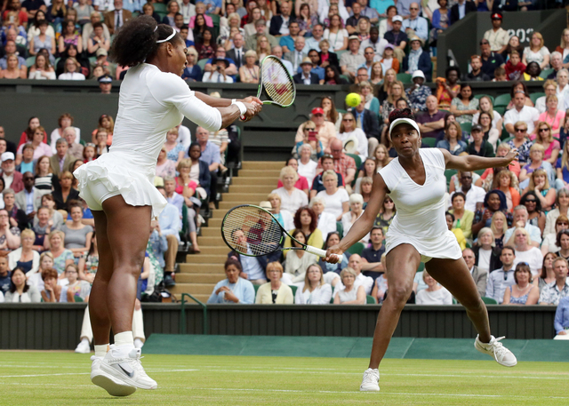 Serena Williams, left, and Venus Williams of the U.S return to Yaroslava Shvedova of Kazahkstan and Timea Babos of Hungary during the women's doubles final during the Wimbledon Tennis Championship ...