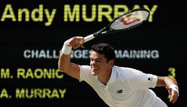 Milos Raonic of Canada plays a return to Andy Murray of Britain during the men's singles final on the fourteenth day of the Wimbledon Tennis Championships in London, Sunday, July 10, 2016. (Ben Cu ...