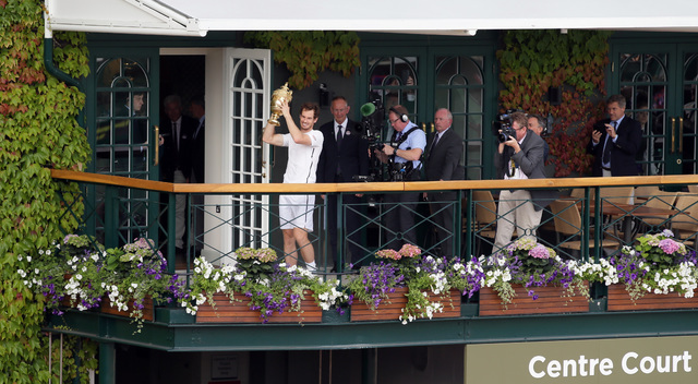 Andy Murray of Britain hold up the trophy after beating Milos Raonic of Canada in the men's singles final on day fourteen of the Wimbledon Tennis Championships in London, Sunday, July 10, 2016. (T ...