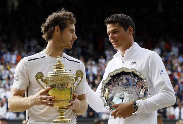 Andy Murray of Britain holds up his trophy after beating Milos Raonic of Canada, right, in the men's singles final on day fourteen of the Wimbledon Tennis Championships in London, Sunday, July 10, ...