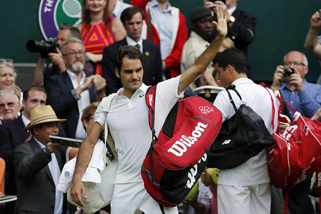Roger Federer of Switzerland, front, walks off the court with Milos Raonic of Canada after being beaten by him in their men's semifinal singles match on day twelve of the Wimbledon Tennis Champion ...