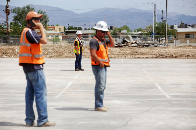 VT Construction employees, from left, Sean Gilbert, Joseph Lesko, and Ed Cheff, watch their co-worker demolishes a portable building at Lincoln Elementary School in North Las Vegas on Tuesday, Jun ...