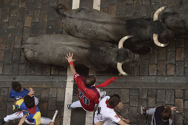 Revelers run with Jose Escolar Gil's fighting bulls as they head towards Estafeta street during the third running of the bulls at the San Fermin Festival, in Pamplona, northern Spain, Saturday, Ju ...