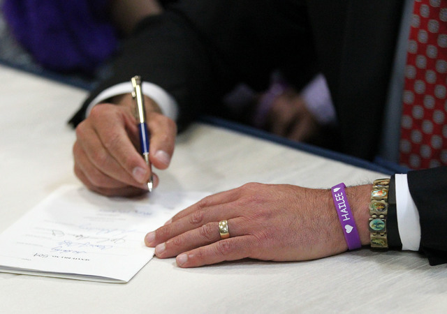Wearing his wristband showing support for White Middle School student Hailee Lamberth who committed suicide, Nevada Gov. Brian Sandoval signs an anti-bullying bill into law at Carson Middle School ...