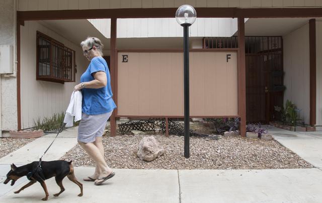Crossroad One condominiums homeowner association president Tori Bridges-Hudson, 69, walks her dog Roman through her complex on Friday, July 29, 2016. Richard Brian/Las Vegas Review-Journal Follow  ...
