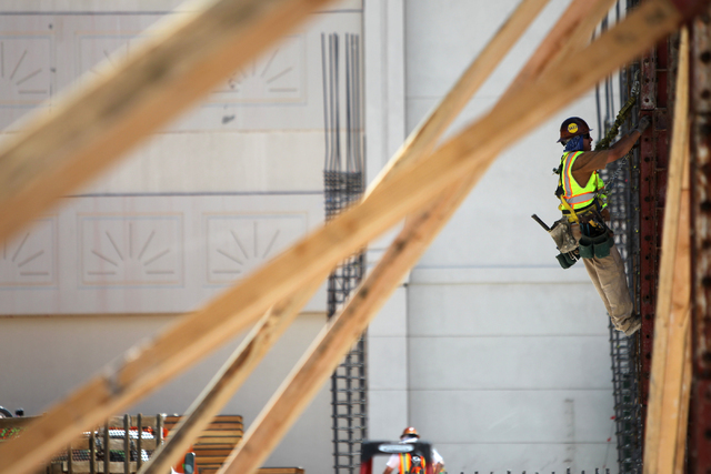 A contraction climbs a steel building column following a presentation hosted by the PENTA Building Group on the safety hazards heat brings at the Lucky Dragon casino-hotel construction site in Las ...