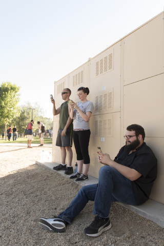 Jeremy Geoffroy, left, Leah Geoffrey, center, and Mason Geiger gather in the shade to play Pokemon Go at Sunset Park in Las Vegas Sunday, July 10, 2016.(Jason Ogulnik/Las Vegas Review-Journal)