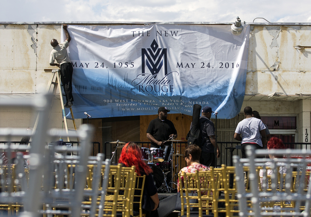 Harry Holmes hangs a banner at the proposed new Moulin Rouge Las Vegas during a ground breaking at the original Moulin Rouge site at 900 W. Bonanza Road on Tuesday, May 24, 2016. (Jeff Scheid/Las  ...
