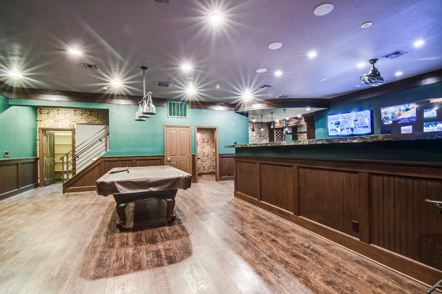 The basement features a bar large enough to seat 10, pool table and powder room. (The Napoli Group)