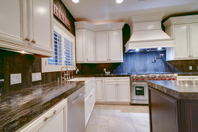 The expresso backsplash and leathered granite counters of the kitchen are offset by white cabinets and travertine floors. Wolf appliances complete the setup for an aspiring or professional chef. ( ...