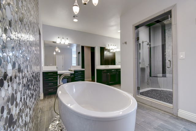 The master bath has split vanities with quartz countertops, an oversized river rock-tiled shower and center-featured spa tub surrounded by a black and white Eskimo pie mosaic-tile backsplash wall. ...
