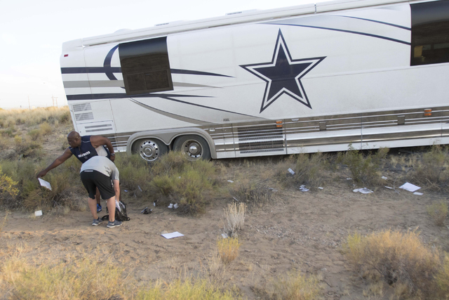 Members of the Dallas Cowboys staff mill around the wreckage involving a Cowboys team bus and a minivan on U.S. Highway 93 near Dolan Springs, Arizona, on Sunday, July 24, 2016. (Richard Brian/Las ...