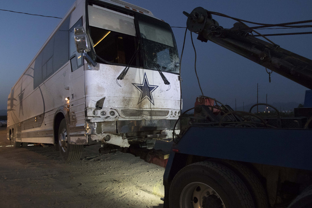 A Dallas Cowboys team bus is loaded on a tow truck after it was involved in a fatal crash with a minivan on U.S. Highway 93 and Pierce Ferry Road in Dolan Springs, Ariz., on Sunday, July 24, 2016. ...