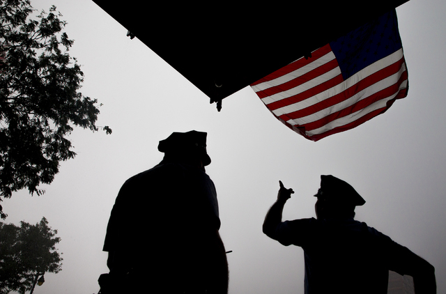 Philadelphia Police Department officers Michael Beck, left, and Juan Delgado take cover under an American flag during a thunderstorm in Philadelphia, Pa. (Benjamin Hager/Las Vegas Review-Journal)