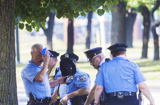 Philadelphia Police Department officers try to cool down in the shade outside the Wells Fargo Center as record temperatures hit Philadelphia, Pa., on Saturday, July 23, 2016. (Benjamin Hager/Las V ...