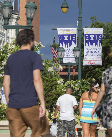 Pedestrians pass by signage for the Democratic National Convention on Market Street on Saturday, July 23, 2016, in Philadelphia, Pa. (Benjamin Hager/Las Vegas Review-Journal)