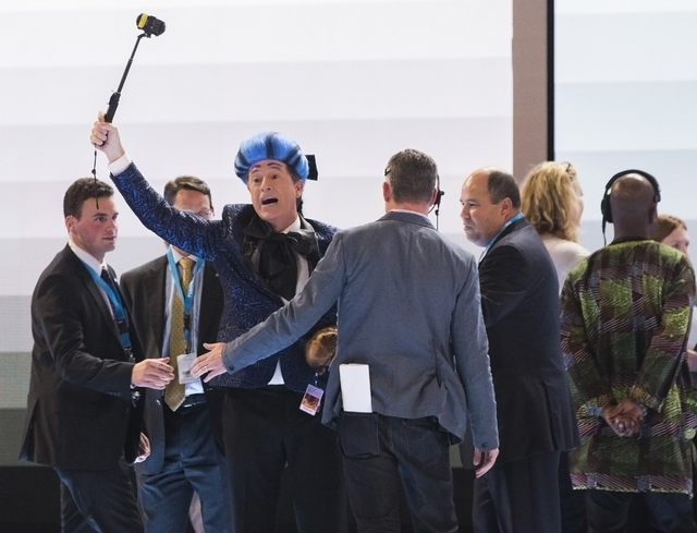 """""""The Late Show"""" host Stephen Colbert, left, dressed as his version of """"The Hunger Games"""" character Caesar Flickerman, gestures toward the crowd as Secret Service agents escort him out on the eve o ..."""