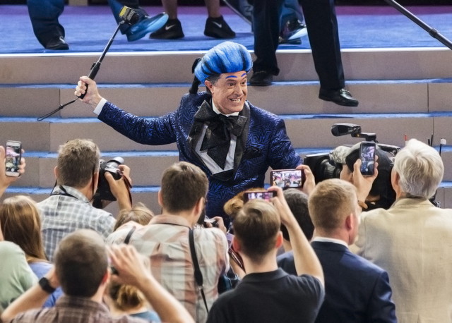 """""""The Late Show"""" host Stephen Colbert, left, dressed as his version of """"The Hunger Games"""" character Caesar Flickerman, interacts with media as Secret Service agents escort him out on the eve of the ..."""