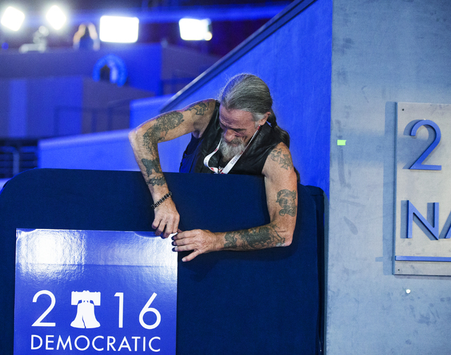 Theatrical carpenter Gary Gort hangs a Democratic National Convention sign on the eve of the DNC at the Wells Fargo Center on Sunday, July 24, 2016, in Philadelphia.  (Benjamin Hager/Las Vegas Rev ...