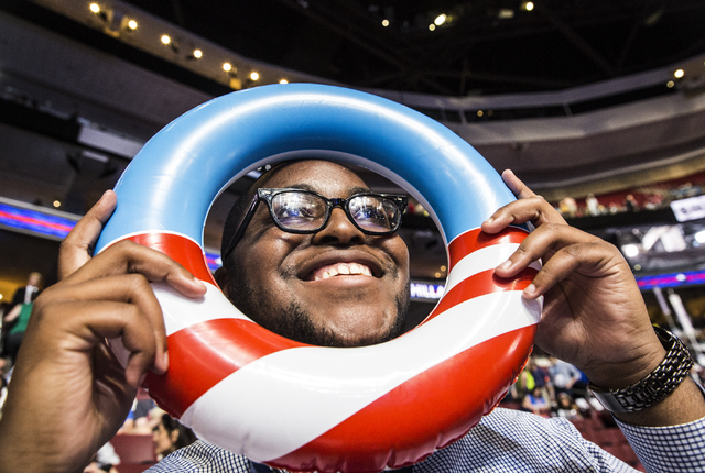 John Easterling peers through an inflatable American flag before the start of the third day of the Democratic National Convention at the Wells Fargo Center on Wednesday, July 27, 2016, in Philadel ...