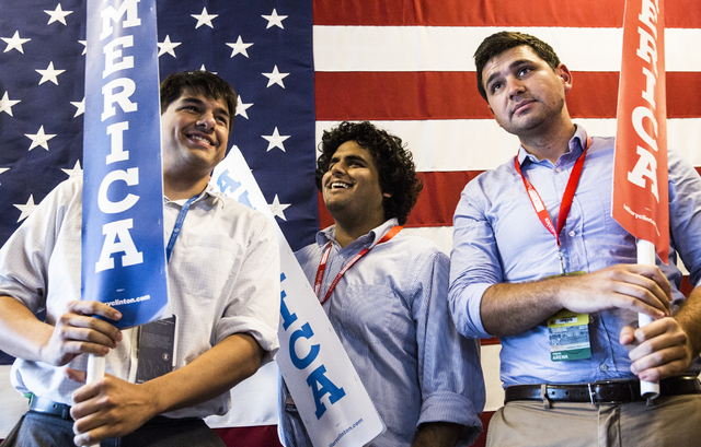 David Byler, left, Get Jeswani and John Dillon Jr. joke around with signage before the start of the third day of the Democratic National Convention at the Wells Fargo Center on Wednesday, July 27, ...
