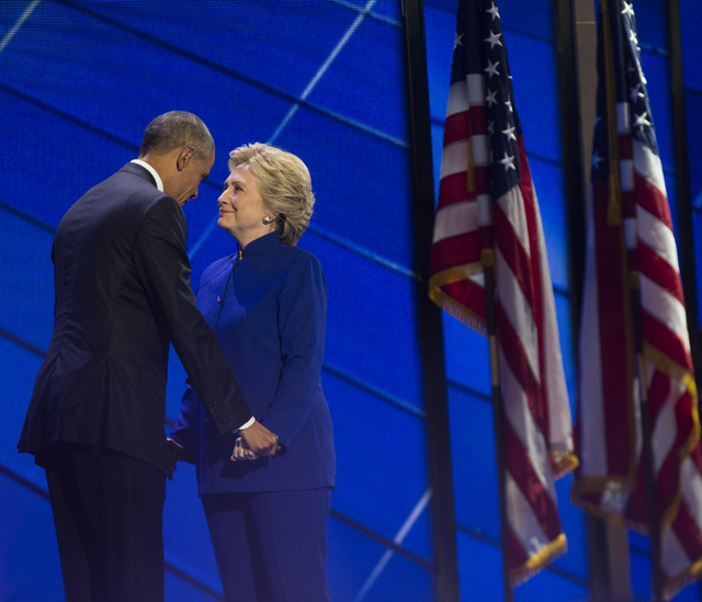 President Barack Obama, left, embraces Hillary Clinton at the conclusion of the third day of the Democratic National Convention at the Wells Fargo Center on Wednesday, July 27, 2016, in Philadelph ...