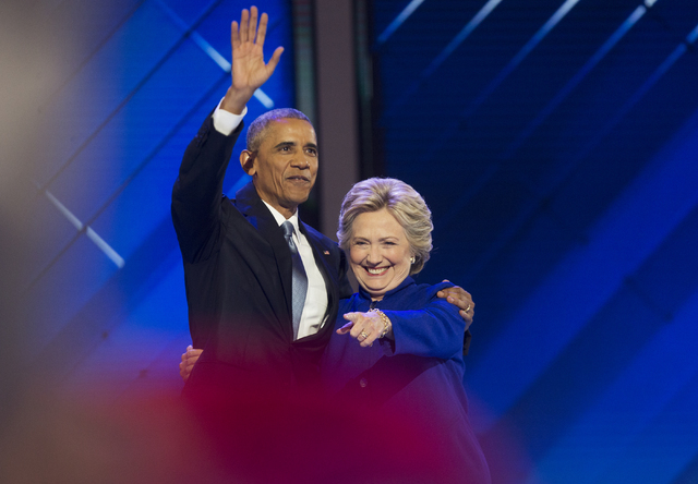 President Barack Obama, left, celebrates with Hillary Clinton at the conclusion of the third day of the Democratic National Convention at the Wells Fargo Center on Wednesday, July 27, 2016, in Phi ...