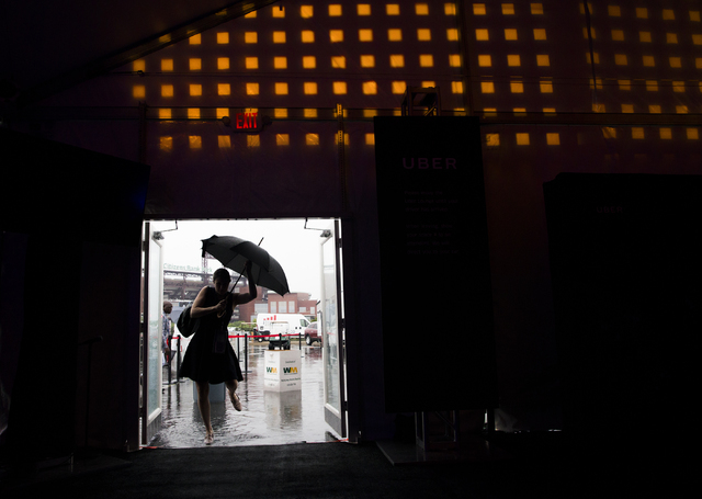 Covention attendees rush to get out of the rain at the Uber tent during the final day of the Democratic National Convention at the Wells Fargo Center on Thursday, July 28, 2016, in Philadelphia. B ...