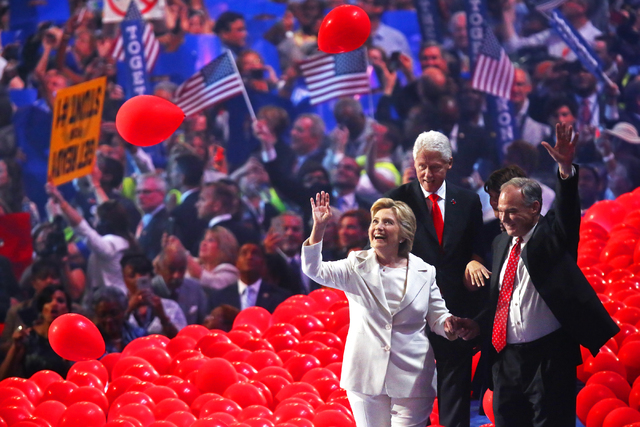Democratic presidential nominee Hillary Clinton, left, former President Bill Clinton and Tim Kaine walk off stage through a sea of balloons during the final day of the Democratic National Conventi ...