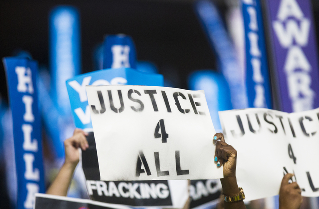 Attendees hold signs demanding legal system reform  during the final day of the Democratic National Convention at the Wells Fargo Center on Thursday, July 28, 2016, in Philadelphia. Benjamin Hager ...