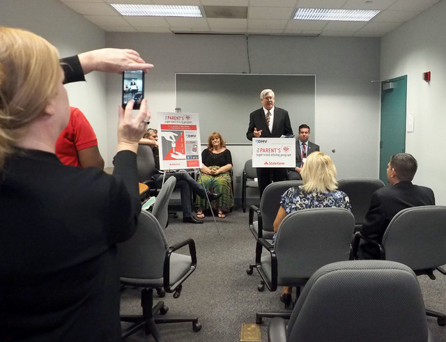 Rita Gallagher takes a photo of Kevin Malone as the Nevada Department of Motor Vehicles unveils a new program, The Parent's Supervised Driving Program, that will help parents teach their teens how ...