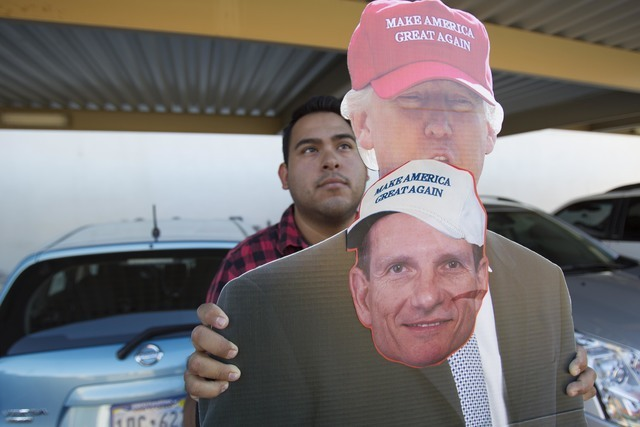 Jose Macias holds a cut out of Republican presidential candidate Donald Trump with U.S. Rep. Joe Heck, R-Nev., on it outside a breakfast meeting. (Richard Brian/Las Vegas Review-Journal) Follow @v ...