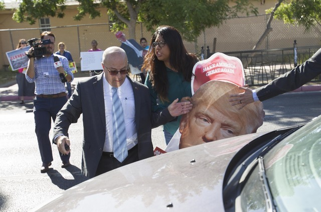 Protester Erika Castro, center, scuffles with security of U.S. Rep. Joe Heck, R-Nev. following at a breakfast meeting hosted by the non-partisan organization Hispanics In Politics. (Richard Brian/ ...