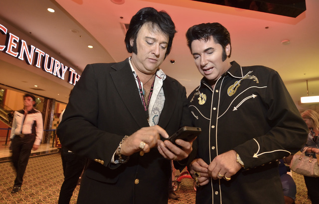 "Jim Westover, left, and Clint Ingbretson check out fellow Elvis tribute artists on Westover's phone at ""Images of the King Las Vegas"" at Sam's Town Live in the Sam's Town hotel-casino at ..."