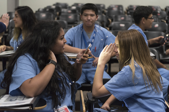 From left, students Rania Mudassar and Kimberly Giannantonio do an exercise to observe the effects of light on pupil size during CampMed at UNLV July 22. Jason Ogulnik/View