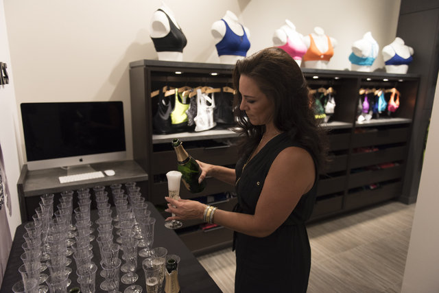 Events with a Twist employee Leann Albertoni pours sparkling wine during a preview event for the Fabletics active wear clothing store at Downtown Summerlin in Las Vegas Thursday, July 21, 2016. Ja ...