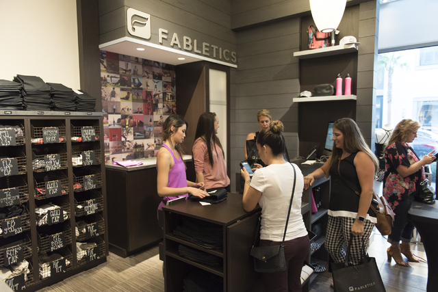 Fabletics employees Mintra Tranpun, left, and Lauren Simmons, second from left, help customers during a preview event for the active wear clothing store at Downtown Summerlin in Las Vegas Thursday ...