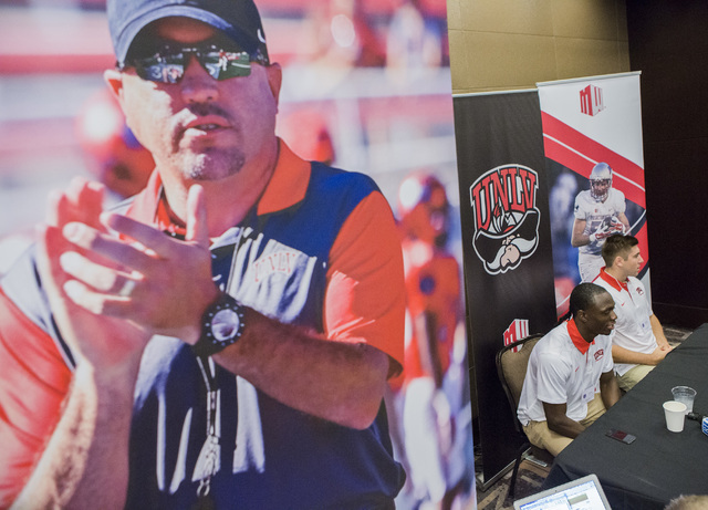 A life size photo of UNLV coach Tony Sanchez is seen while UNLV football players wide receiver Devonte Boyd, left, and linebacker Ryan McAleenan discuss the upcoming season Wednesday, July 27, 201 ...