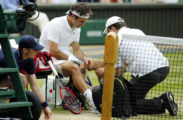 In this July 8, 2016, file photo, Roger Federer of Switzerland receives medical attention during his men's semifinal singles match against Milos Raonic of Canada at the Wimbledon Tennis Championsh ...