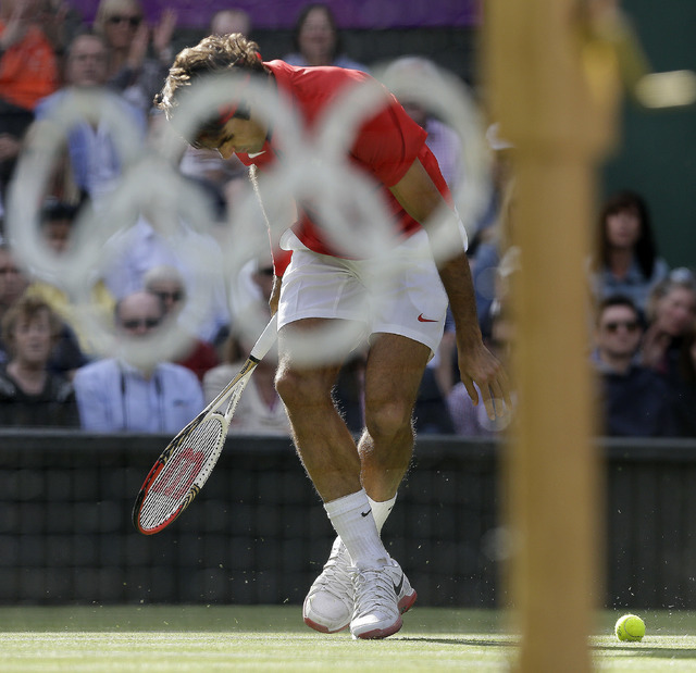 In this Aug. 2, 2012, file photo, Roger Federer of Switzerland loses a point to John Isner of the United States at the All England Lawn Tennis Club in Wimbledon, London at the 2012 Summer Olympics ...