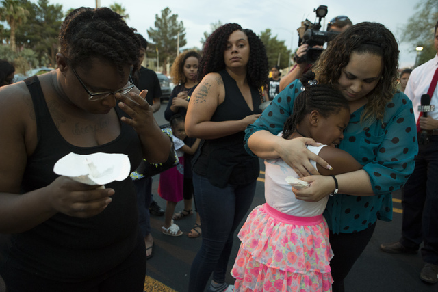 Shanelle Garbutt, far right, embraces her student Lehairah Jackson, who was a classmate of 9-year-old murder-suicide victim Anhurak Dej-Oudom, during a candlelight vigil for the victims of a murde ...