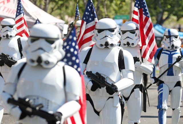 Parade participants march as Star Wars Stormtroopers representing the Neon City Garrison chapter of the 501st Legion during the 22nd Annual Summerlin Council Patriotic Parade Monday, July 4, 2016, ...