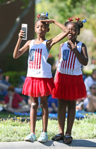 Erin Bajadali, 8, left, salutes parade participants as her sister Lauren, 6, watches next to her side during the 22nd Annual Summerlin Council Patriotic Parade Monday, July 4, 2016, in Las Vegas.  ...