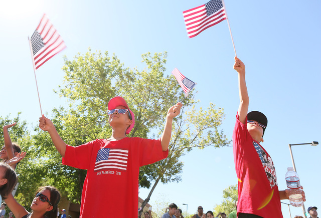Nia Chen, 8, left and her brother Ian, 7, wave flags during the 22nd Annual Summerlin Council Patriotic Parade Monday, July 4, 2016, in Las Vegas. (Ronda Churchill/Las Vegas Review-Journal)