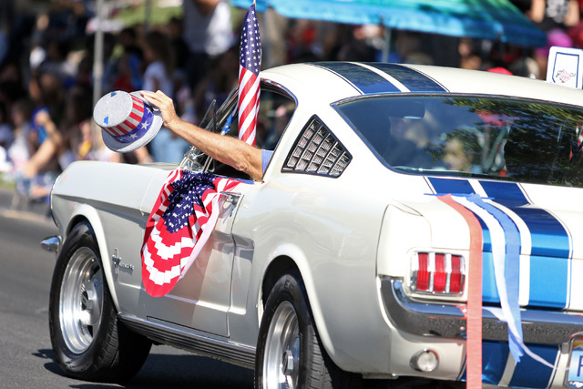 A driver in a procession with the classic Mustangs waves a patriotic hat during the 22nd Annual Summerlin Council Patriotic Parade Monday, July 4, 2016, in Las Vegas. (Ronda Churchill/Las Vegas Re ...