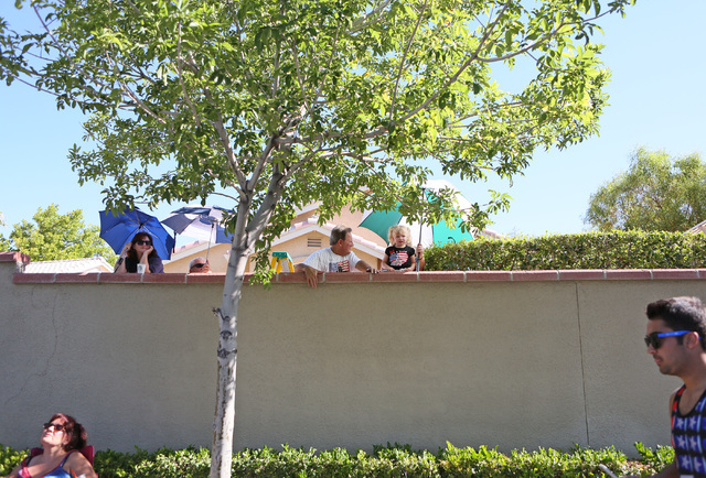 People peak over residential walls to view the 22nd Annual Summerlin Council Patriotic Parade Monday, July 4, 2016, in Las Vegas. (Ronda Churchill/Las Vegas Review-Journal)