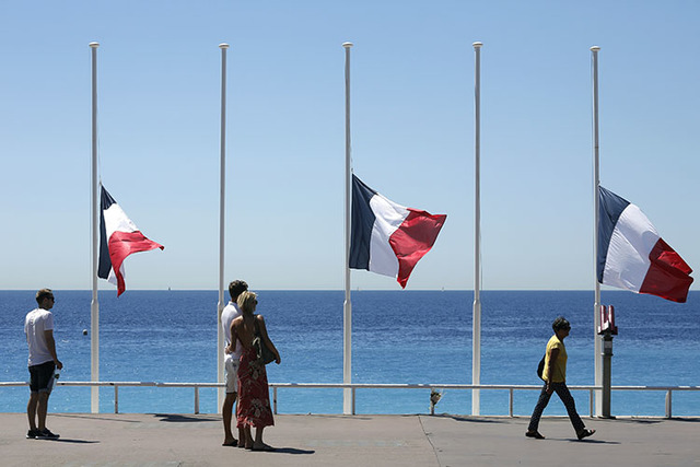 People stroll on the Promenade des Anglais with the French flag at half mast, near the scene of a truck attack in Nice, southern France, Saturday, July 16, 2016. (Laurent Cipriani/The Associated P ...
