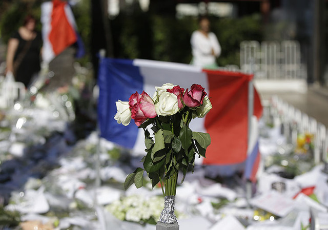 Floral and papers tributes are laid with a French flag near the scene of a truck attack in Nice, southern France, Saturday, July 16, 2016. (Luca Bruno/The Associated Press)
