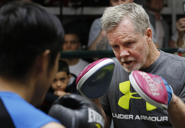 Trainer Freddie Roach spars with Zou Shiming, a two-time Olympic gold medalist and three-time World Amateur Champion from China, Wednesday, June 8, 2016, at Mendez Gym in New York. (Mark Lennihan/AP)